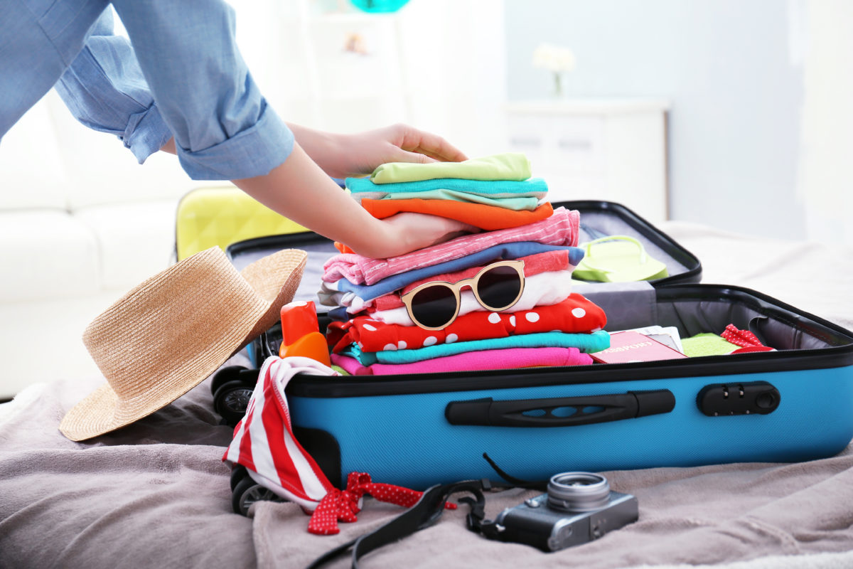 Female hands packing a suitcase for a holiday in Devon