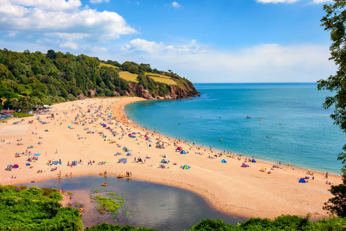A sunny seascape with people enjoying the beach at Blackpool sands near Dartmouth in Devon