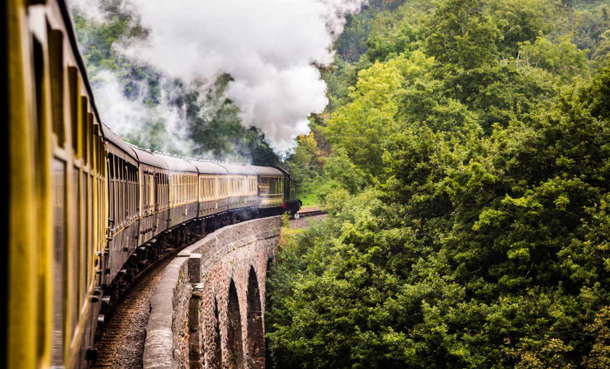 Carriages of Dartmouth Steam Railway travelling along viaduct in South Devon countryside