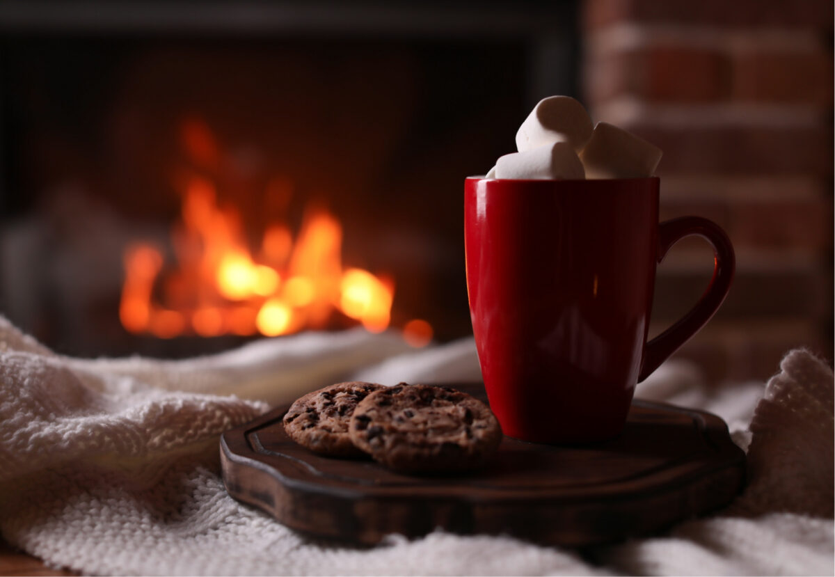 Mug of hot chocolate in front of fire place in cosy Devon cottage