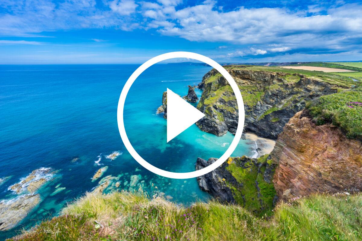 Play button over image of sunny South Devon coastline