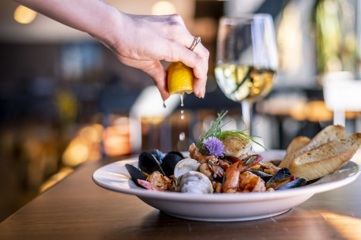 Hand squeezes lemon over plate of seafood in restaurant