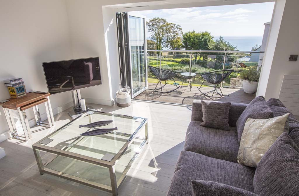 Living area with folding doors onto balcony of Windjammer holiday let with sea views in Devon