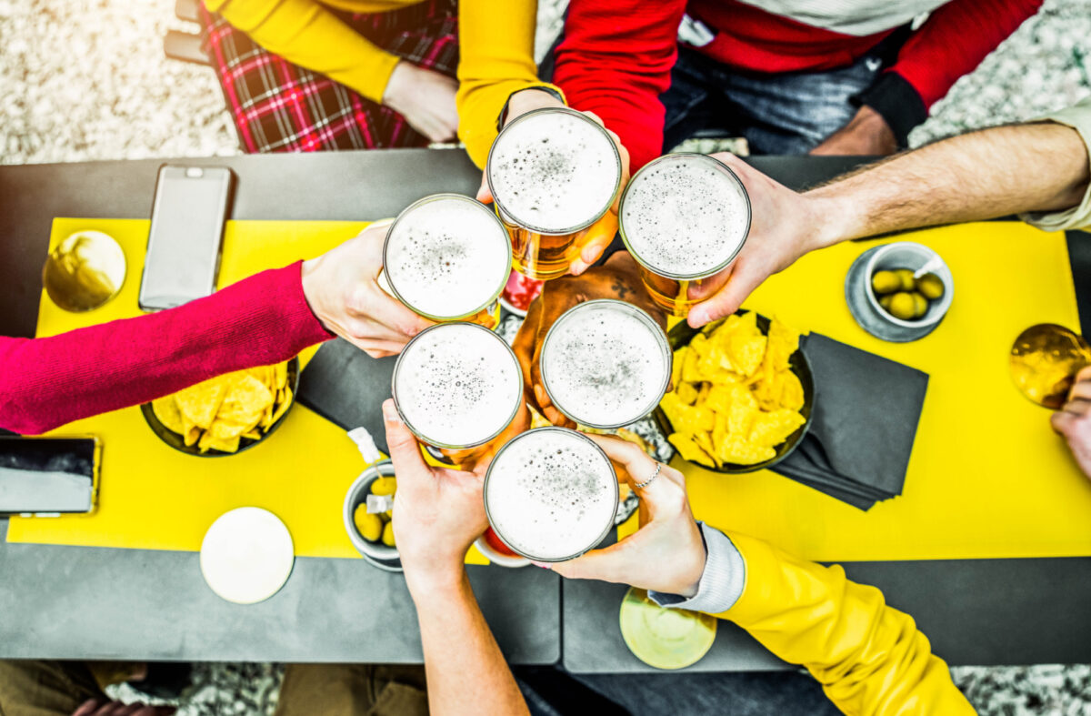 Six friends having a toast with beers in a pub garden