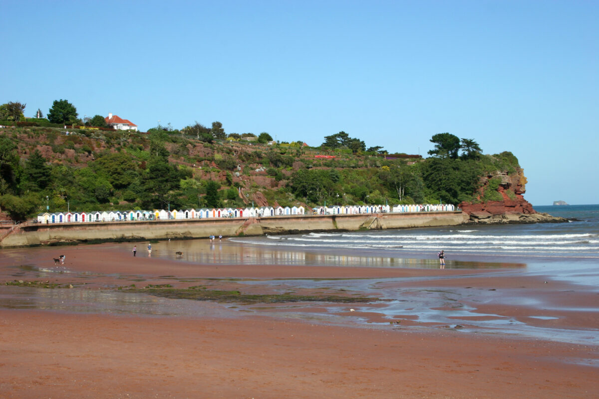 Beach huts lining the red sands of Goodrington North Beach