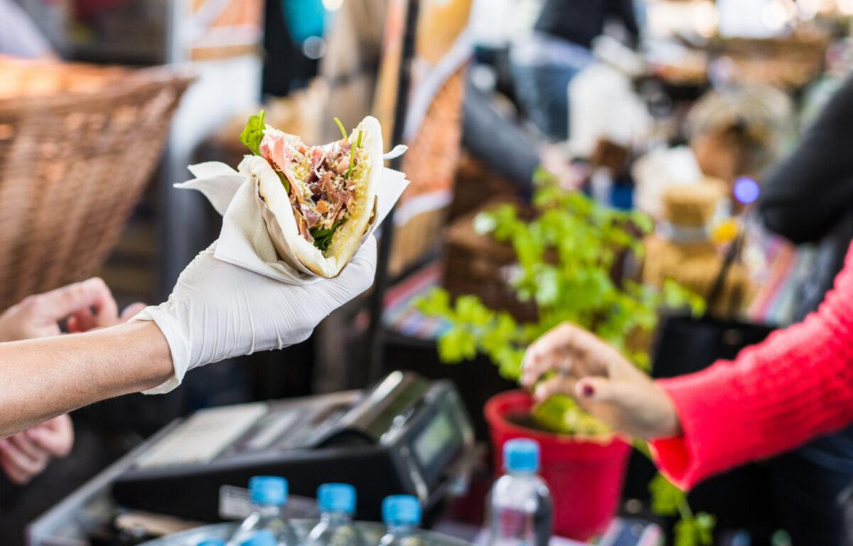 Chef passing tortilla to customer at food festival